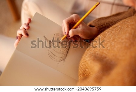 halloween, holidays and leisure concept - close up og young woman with pencil drawing picture of pumpkin in sketchbook or diary at home