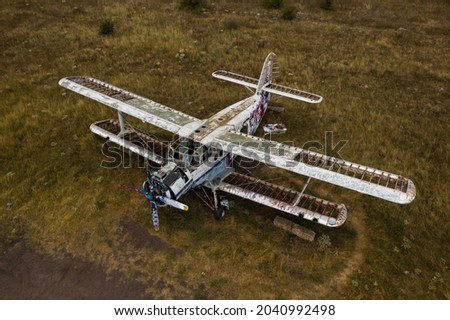 An old abandoned small airplane in the field Royalty-Free Stock Photo #2040992498
