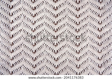 Beautiful knitted pattern of beige-brown wool. Textile background with an ornament for banners,postcards, interior and decor elements, website, wallpaper, as a sample for knitting at courses