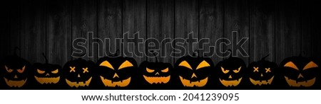 HALLOWEEN background banner wide panoramic panorama template -Silhouette of scary carved luminous cartoon pumpkins, isolated on dark black wooden boards wood wall texture