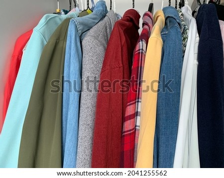 Outerwear hanging in the closet on hangers, colorful things of different shades for different seasons, close-up Royalty-Free Stock Photo #2041255562