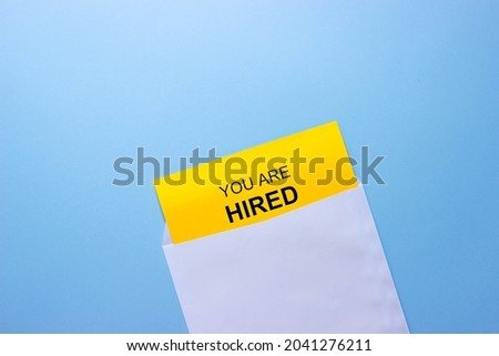 Opened white envelope with you are ( You're ) hired yellow note on blue background, top view. Business and recruitments concepts