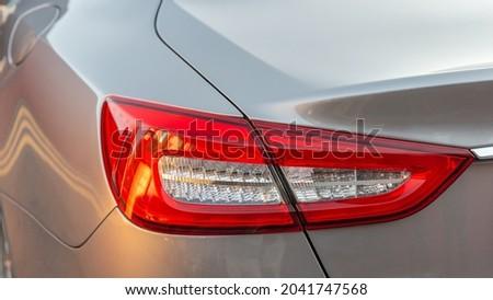 The red headlight of a modern sedan metallic car. Rear stop light. Premium LED sedan taillights. Royalty-Free Stock Photo #2041747568