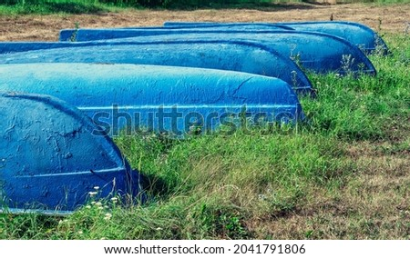 A group of blue wooden boats lies upside down on the green grass. Selective focus, graphic resource.
