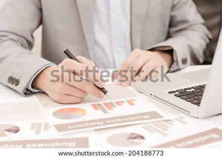 Businessman analyzing investment charts with laptop. Accounting #204188773