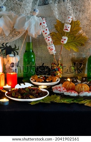 Decorating themed buffet table with Halloween sweets in vertical photo format. Selection sweet appetizers, drink themed Halloween. Party food table. Halloween themed food table for spooky party.
