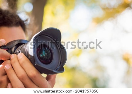 Close-up photo of young professional photographer shooting something or someone in autumn park. Fall photo session