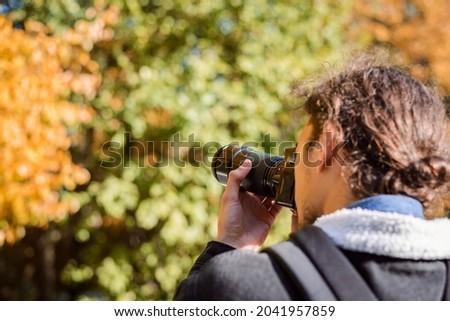 Back photo of photographer shooting autumn park. Concept of depicting fall season on photos