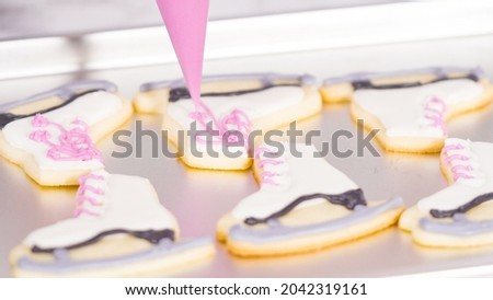 Icing figure skate shaped sugar cookies with royal icing.