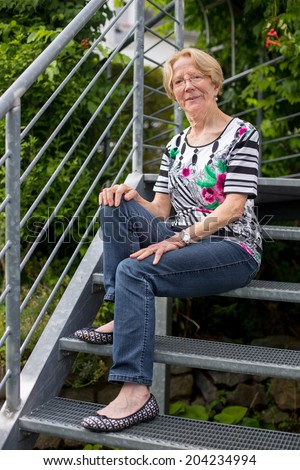 A nice elderly woman smiles sits on stairs in a garden and smile #204234994