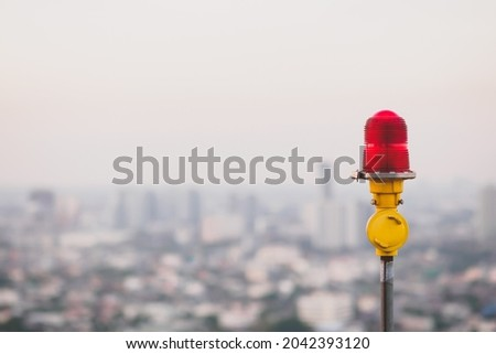 Red lantern of obstruction lights, mounted on the rooftop of  high rise tall building to ensure flights safety and warn the danger for the plane, located against the background of the city, copyspace Royalty-Free Stock Photo #2042393120