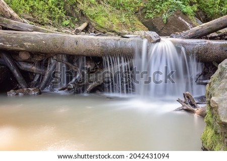 Smooth water and stones, river and wild nature, mountains, little waterfall Royalty-Free Stock Photo #2042431094