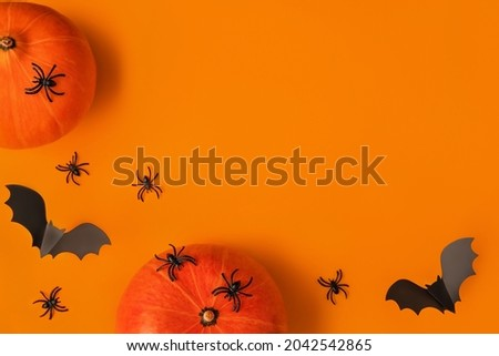 Halloween composition of pumpkins and cartoon black bats and spiders on orange background. Bright holiday backdrop for your design. Creative trendy flat lay with place for text.