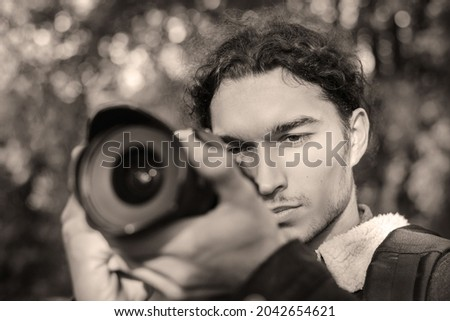 Black and white photo of photographer shooting someone in the park. Shooting photos in the park