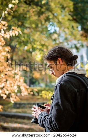 Side photo of concentrated male photographer looking through photos on his camera. Shooting beautiful colorful pictures of fall park