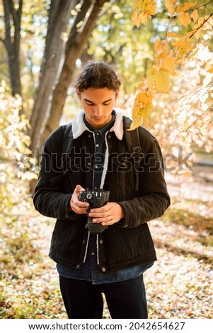Photographer shooting pictures in autumn park. Portrait of photographer with modern camera looking through shot photos