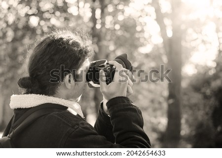 Black and white photo of photographer in autumn park shooting fall landscapes. Photographer concept
