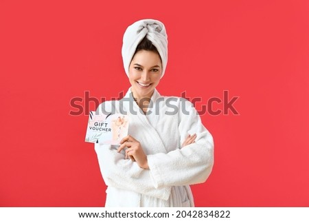 Young woman with gift voucher for massage on color background
