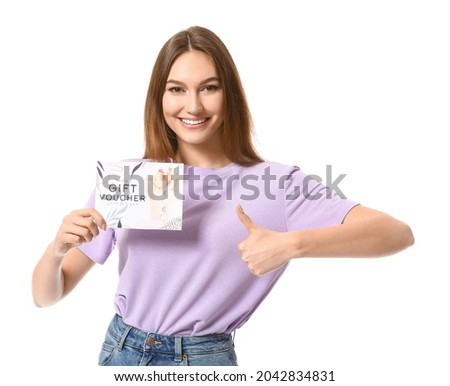 Young woman with gift voucher for massage showing thumb-up on white background