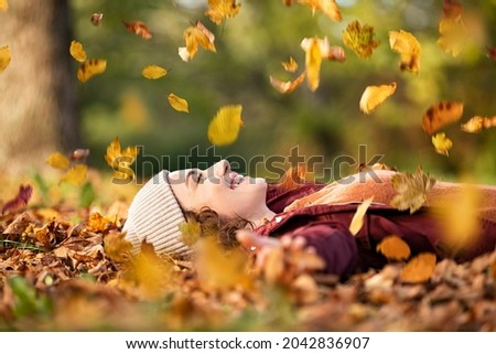 Cheerful young woman lying over leaves with closed eyes and smiling. Woman lying over autumn ground relaxing at park. Casual joyful girl having fun throwing leaves in autumn park with copy space. Royalty-Free Stock Photo #2042836907