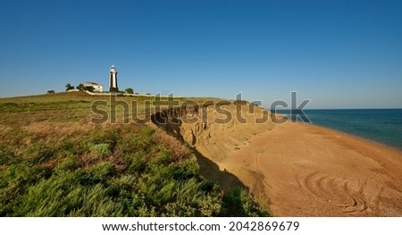 Desolate sandy shore with a lighthouse in the ocean. Royalty-Free Stock Photo #2042869679