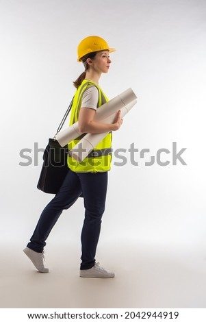 Builder with papers. Woman builder steps on white background. Concept she is inspecting construction site. Work as construction inspector. Construction company inspection. Engineer in yellow uniform