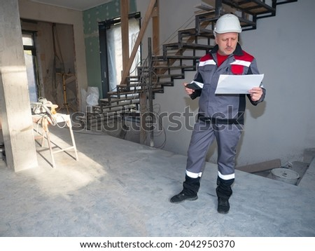 Repairman inside a house under construction. Repairman in uniform with blueprints in his hands. Man in a construction worker uniform. Career as apartment renovator. He examines a sheet of paper Royalty-Free Stock Photo #2042950370