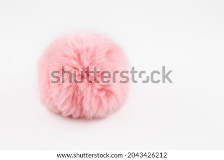 A fluffy ball of pink faux fur on a white background. Pompon. A toy for a cat. Decoration and decor of clothes. Eco-fur ball, soft and pleasant to the touch Royalty-Free Stock Photo #2043426212