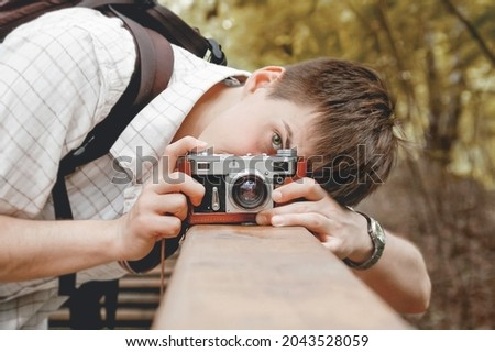 Young man takes a shoot with old fashioned film camera. Handsome man in autumn park. Photographer with retro photo camera. Fall season.