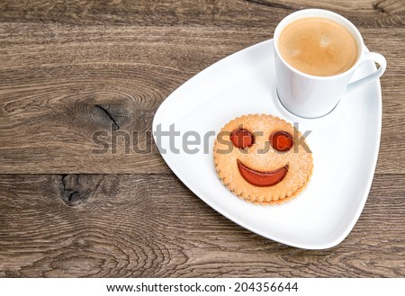 coffee with smiled cookie on wooden background. funny breakfast