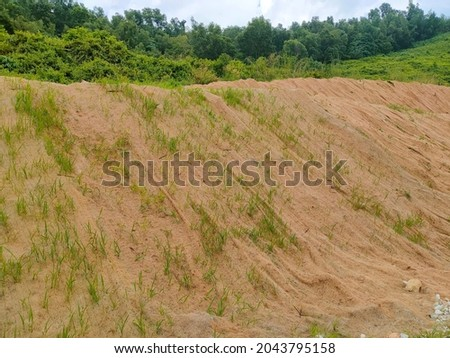 Permanent slope protection with grass using the hydroseed method. The grass used to stabilizes the slope structure and prevent slope erosion. Effective and less maintenance.  Royalty-Free Stock Photo #2043795158