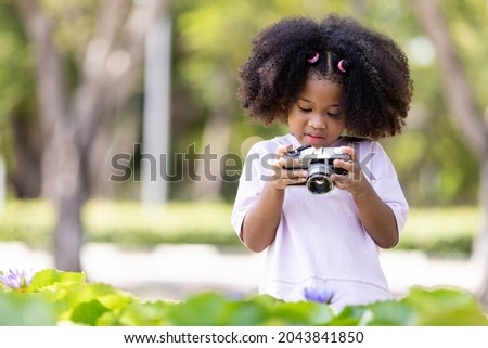 Cute afro curly girl Young women take pictures of old cameras Taking lotus flowers in the garden, Nature study concept.