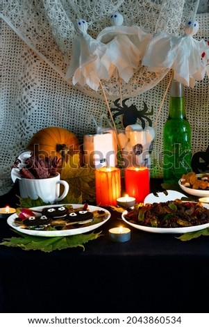 Vertical photo decorating themed buffet table with Halloween. Selection sweet appetizers, drink themed Halloween.  Pumpkin, sweets and cookies on table. Happy Halloween! Preparation holiday.