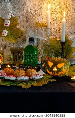 Example decorating themed buffet table with Halloween sweets in vertical photo format. Selection sweet appetizers, drink themed Halloween. Festive home Halloween themed food, decor. Party food table.