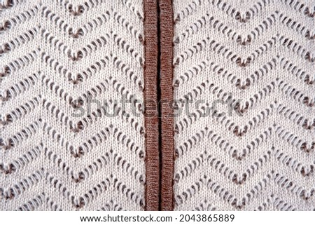 An element of a knitted wool jumper with a zipper with a beautiful beige-brown pattern.Textile background with an ornament for banners,postcards, a website, as a sample for knitting at courses