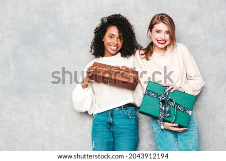 Two young beautiful smiling international hipster female in trendy clothes.Sexy carefree women posing near gray wall.Positive models hugging and giving each other gift boxes.Christmas, x-mas, concept Royalty-Free Stock Photo #2043912194