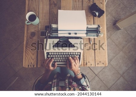 Top view of woman hands typing on typewriter keypad on paper. Woman typing on old typewriter keypad at office desk with coffee mug and camera on table Royalty-Free Stock Photo #2044130144