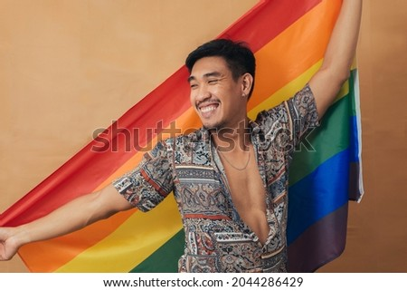 Happy man smiling and standing with pride flag. Gender Equality and LGBTQ concept.