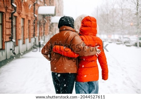 Back view of anonymous women in outerwear hugging each other and walking on snowy city street on winter day Royalty-Free Stock Photo #2044527611