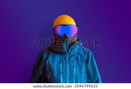 Snowboarder in full outerwear isolated over a dark purple background. Winter sports fashion.  Royalty-Free Stock Photo #2044799633