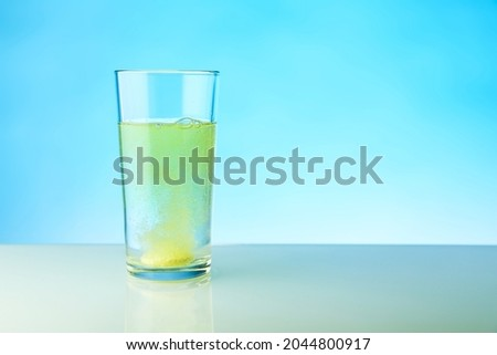 dissolving tablet dissolves in water on blue background, studio shot. the medicine pill dissolves in a glass of water
