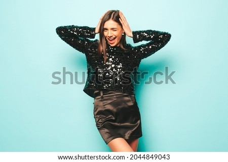 Young beautiful smiling brunette female in nice trendy black evening party clothes.Sexy carefree woman posing near blue wall in studio.Fashionable model with bright evening makeup having fun. Dancing