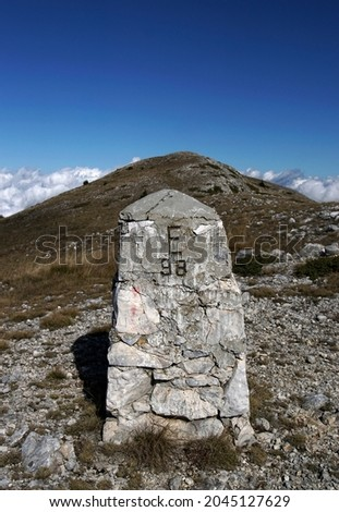 Boundary pyramid on the border between Bulgaria and Greece. View from Slavyanka mountain. Peaks in sunny autumn day. Royalty-Free Stock Photo #2045127629