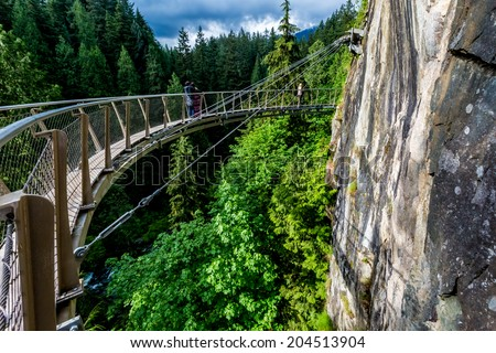 Beautiful Capilano Cliff Walk Suspension Bridge with Tourists Enjoying the View, in Vancouver. Royalty-Free Stock Photo #204513904
