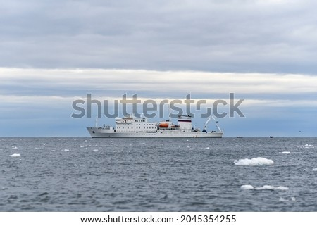 Expedition ship in Arctic sea with ice. White research vessel. Royalty-Free Stock Photo #2045354255