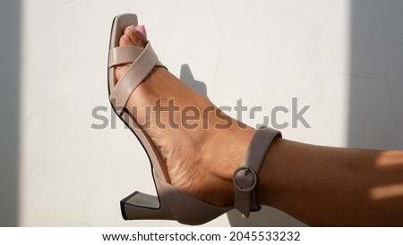 Women's legs in model sandals with heels raised up against a white background. The girl moves her legs in beautiful high-heeled sandals. Beautiful women's shoes, fitting Royalty-Free Stock Photo #2045533232