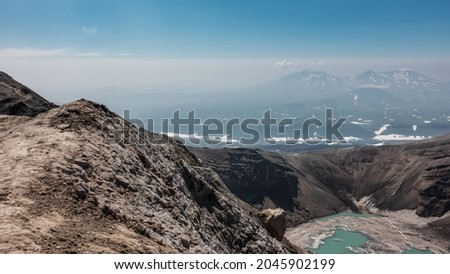 There is a turquoise acid lake in the crater of the volcano. The snow is melting on the banks. High steep slopes. Mountains with snow-covered slopes are visible against the blue sky. Kamchatka.Gorely  Royalty-Free Stock Photo #2045902199