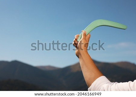 Man throwing boomerang in mountains, closeup. Space for text Royalty-Free Stock Photo #2046166949