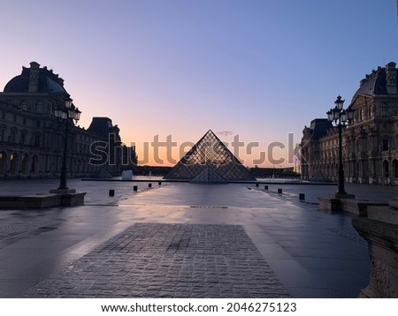 Silhouette of the Louvre in Paris France, with the sunset spilling its last golden rays of light faintly onto the courtyard.   Royalty-Free Stock Photo #2046275123