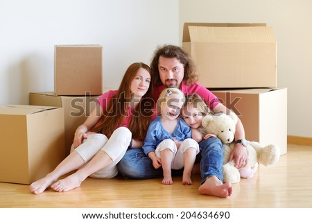 Happy young family sitting on a floor in their new home #204634690